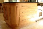 French oak, rounded corner unit with black granite worktop.